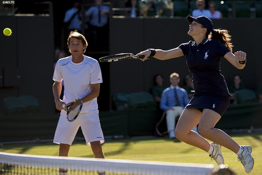 """A ball girl hits a volley after invitation doubles player Paul Haarhuis invited her to play a point to replace his partner at the All England Lawn and Tennis Club in London, England Thursday, July 3, 2014 during the 2014 Championships Wimbledon."""
