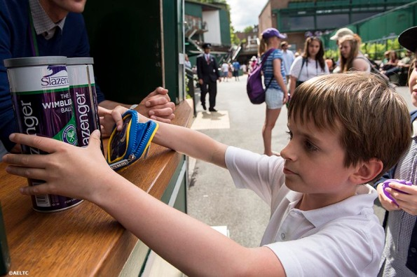 """A boy grabs two cans of Slazenger used championship tennis balls at the All England Lawn and Tennis Club in London, England Tuesday, July 1, 2014 during the 2014 Championships Wimbledon."""