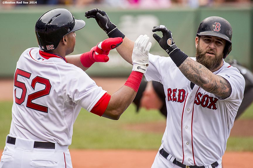 """Boston Red Sox first baseman Mike Napoli high fives left fielder Yoenis Cespedes after hitting a two-run home run to drive in Cespedes after his first at bat as a member of the Boston Red Sox during the second inning of a game against the New York Yankees Saturday, August 2, 2014 at Fenway Park in Boston, Massachusetts."""