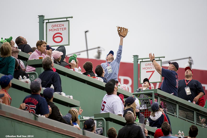 """Fans in the Green Monster seats reach for a home run ball during a game between the Boston Red Sox and the New York Yankees Saturday, August 2, 2014 at Fenway Park in Boston, Massachusetts."""