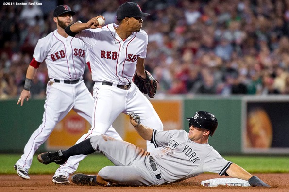 """""""oston Red Sox shortstop Xander Bogaerts and second baseman Dustin Pedroia turn a double play over left fielder Brett Gardner during the first inning of a game against the New York Yankees Sunday, August 3, 2014 at Fenway Park in Boston, Massachusetts."""""""