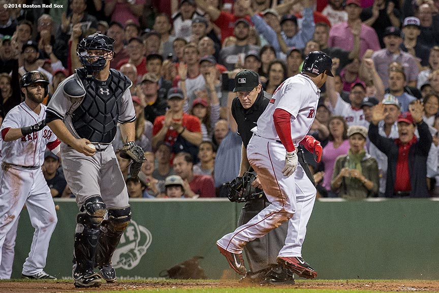"""Boston Red Sox left fielder Yoenis Cespedes jumps as he scores on a double by right fielder Daniel Nava during the first inning of a game against the New York Yankees Sunday, August 3, 2014 at Fenway Park in Boston, Massachusetts."""
