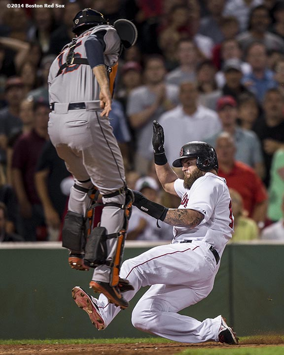 """Boston Red Sox first baseman Mike Napoli slides into home plate during the fourth inning of a game against the Houston Astros at Fenway Park in Boston, Massachusetts Thursday, August 14, 2014."""