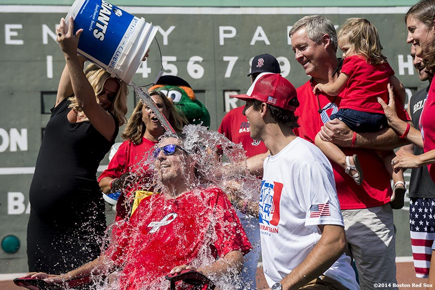 """Former Boston College Baseball player Pete Frates, who lives with ALS, accepts the Ice Bucket Challenge to raise awareness for ALS alongside family members and Boston Red Sox manager John Farrell, third baseman Will Middlebrooks, second baseman Dustin Pedroia, and catcher David Ross at Fenway Park in Boston, Massachusetts Thursday, August 14, 2014."""