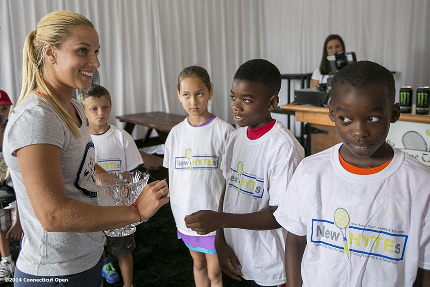 """Kids from the New HYTEs youth development organization draw chips from Dominika Cibulkova during the draw ceremony at the 2014 Connecticut Open at the Yale University Tennis Center in New Haven, Connecticut Friday, August 15, 2014."""