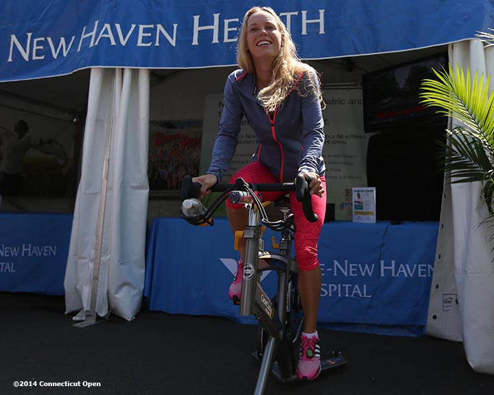 """Caroline Wozniacki bikes on a spin bike in front of the Yale New Haven Health booth during WTA All-Access Hour on day three of the 2014 Connecticut Open at the Yale University Tennis Center in New Haven, Connecticut Sunday, August 17, 2014."""