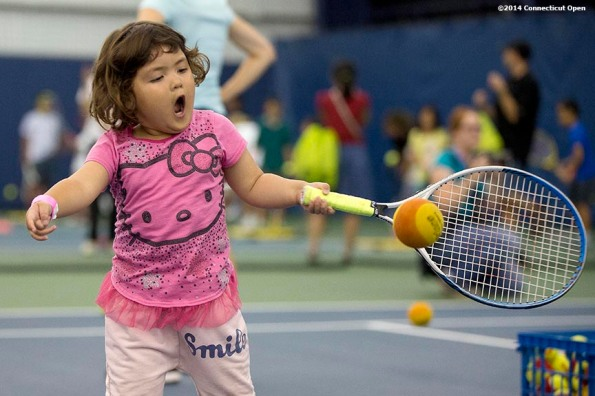 """""""A young fan hits a tennis ball during a tennis clinic as part of Kids Day on day three of the 2014 Connecticut Open at the Yale University Tennis Center in New Haven, Connecticut Sunday, August 17, 2014."""""""