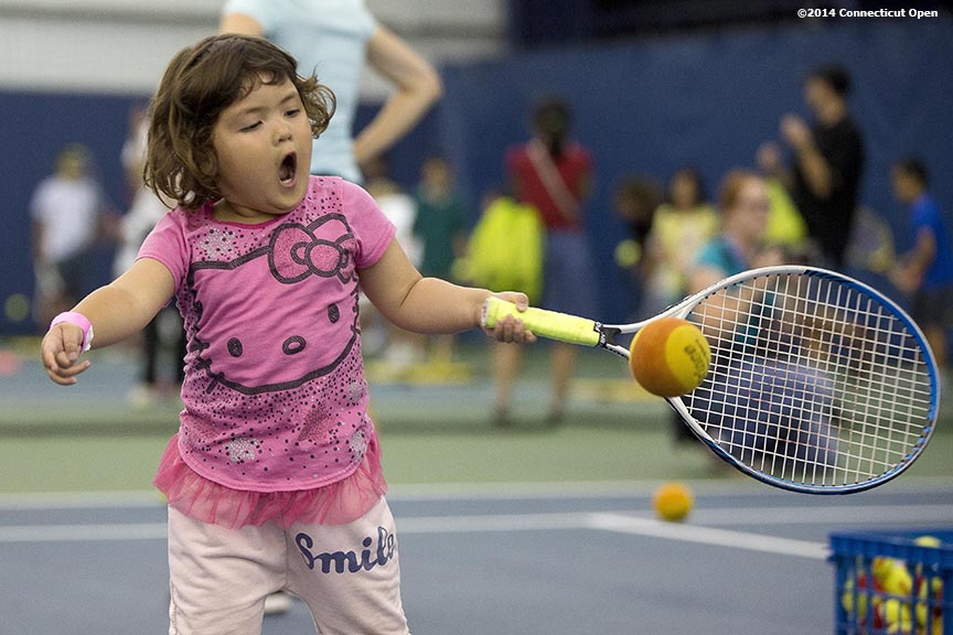 """A young fan hits a tennis ball during a tennis clinic as part of Kids Day on day three of the 2014 Connecticut Open at the Yale University Tennis Center in New Haven, Connecticut Sunday, August 17, 2014."""