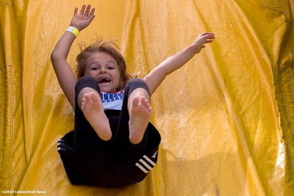"""""""A young fan slides down a slide during a tennis clinic in the AETNA FitZone as part of Kids Day on day three of the 2014 Connecticut Open at the Yale University Tennis Center in New Haven, Connecticut Sunday, August 17, 2014."""""""