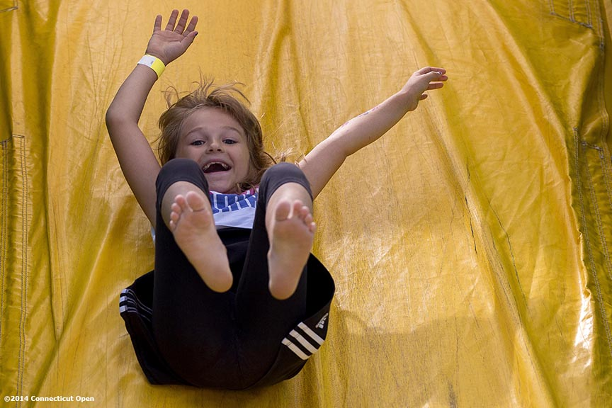 """A young fan slides down a slide during a tennis clinic in the AETNA FitZone as part of Kids Day on day three of the 2014 Connecticut Open at the Yale University Tennis Center in New Haven, Connecticut Sunday, August 17, 2014."""
