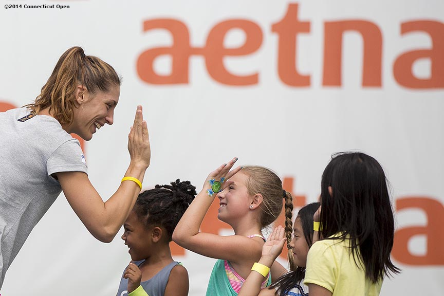 """Andrea Petkovic high fives kids during a tennis clinic in the AETNA FitZone as part of Kids Day on day three of the 2014 Connecticut Open at the Yale University Tennis Center in New Haven, Connecticut Sunday, August 17, 2014."""