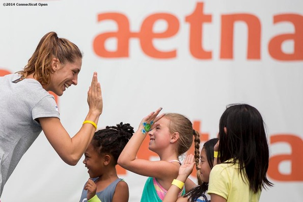 """""""Andrea Petkovic high fives kids during a tennis clinic in the AETNA FitZone as part of Kids Day on day three of the 2014 Connecticut Open at the Yale University Tennis Center in New Haven, Connecticut Sunday, August 17, 2014."""""""