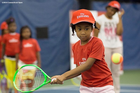 """""""A boy hits a forehand during the Emirates Airline tennis clinic on day five of the 2014 Connecticut Open at the Yale University Tennis Center in New Haven, Connecticut Tuesday, August 19, 2014."""""""