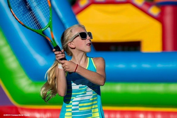 """""""A girl hits a tennis ball during a Girl Scout Night clinic on day five of the 2014 Connecticut Open at the Yale University Tennis Center in New Haven, Connecticut Tuesday, August 19, 2014."""""""