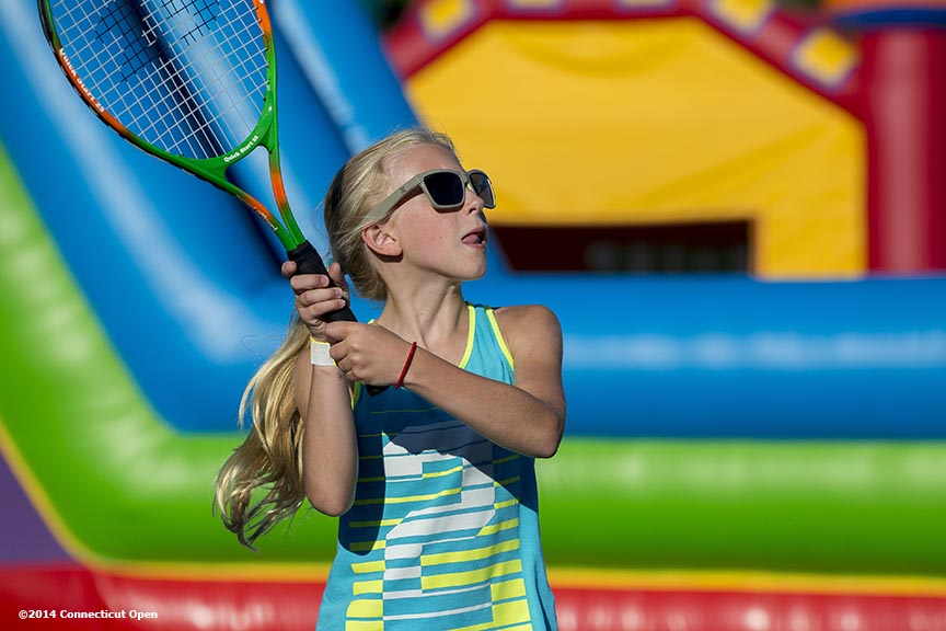 """A girl hits a tennis ball during a Girl Scout Night clinic on day five of the 2014 Connecticut Open at the Yale University Tennis Center in New Haven, Connecticut Tuesday, August 19, 2014."""
