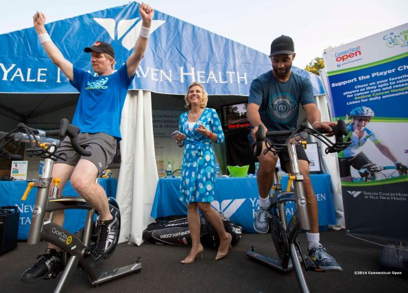 """Jim Courier and James Blake ride spin bikes at the Yale New Haven Health booth during the Men's Legends Event on day six of the 2014 Connecticut Open at the Yale University Tennis Center in New Haven, Connecticut Wednesday, August 20, 2014."""