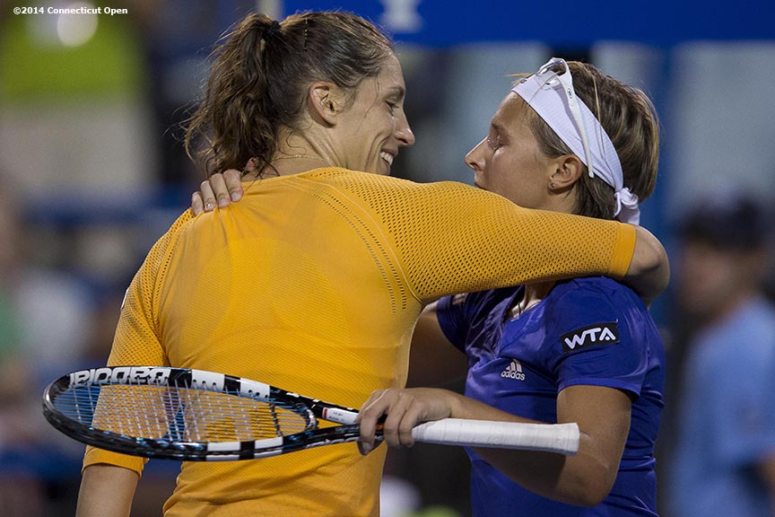 """Andrea Petkovic and Kirsten Flipkens hug at net after Flipkens beat Petkovic in three sets on day six of the 2014 Connecticut Open at the Yale University Tennis Center in New Haven, Connecticut Tuesday, August 19, 2014."""
