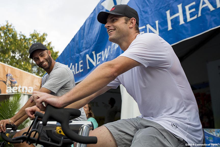 """James Blake and Andy Roddick ride spin bikes for Yale New Haven Health during the Men's Legends Event on day seven of the 2014 Connecticut Open at the Yale University Tennis Center in New Haven, Connecticut Thursday, August 21, 2014."""