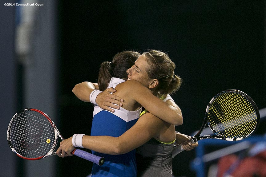 """Marina Erakovic and Arantxa Parra Santonja hug after winning the women's doubles semi-finals against Monica Niculescu and Caroline Garcia on day eight of the 2014 Connecticut Open at the Yale University Tennis Center in New Haven, Connecticut Friday, August 22, 2014."""