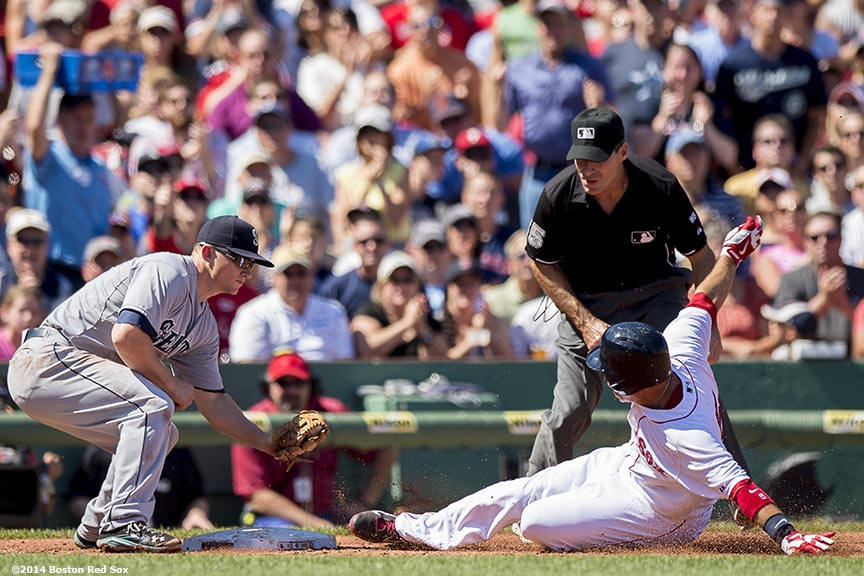 """Boston Red Sox right fielder Allen Craig slides into third base during the first inning of a game against the Seattle Mariners at Fenway Park in Boston, Massachusetts Sunday, August 24, 2014."""