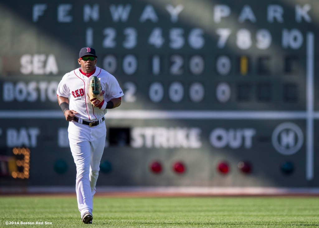 """Boston Red Sox left fielder Yoenis Cespedes runs in front of the Green Monster scoreboard during the eighth inning of a game against the Seattle Mariners at Fenway Park in Boston, Massachusetts Sunday, August 24, 2014."""