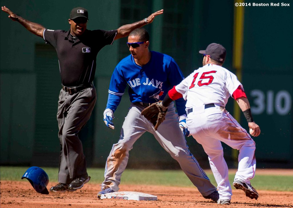"""Boston Red Sox second baseman Dustin Pedroia applies a tag on left fielder Kevin Pillar during second the inning of a game against the Toronto Blue Jays Sunday, September 7, 2014 at Fenway Park in Boston, Massachusetts."""