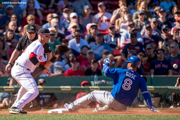 """Boston Red Sox third baseman Will Middlebrooks fields a throw as center fielder Anthony Gose slides into first base during the fifth inning of a game against the Toronto Blue Jays Sunday, September 7, 2014 at Fenway Park in Boston, Massachusetts."""