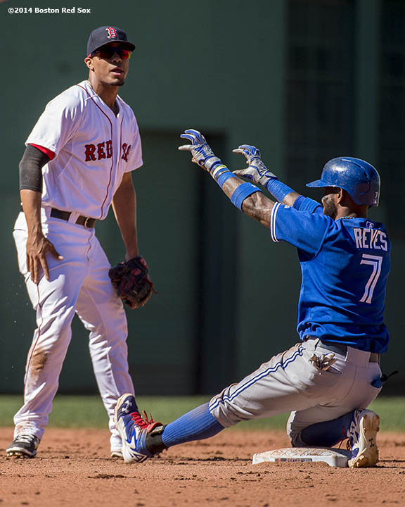 """Boston Red Sox shortstop Xander Bogaerts reacts as shortstop Jose Reyes gestures toward the dugout after reaching second base on an error during the fifth inning of a game against the Toronto Blue Jays Sunday, September 7, 2014 at Fenway Park in Boston, Massachusetts."""