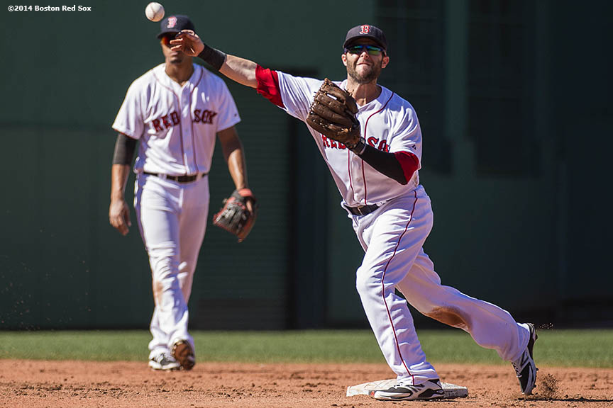 """Boston Red Sox second baseman Dustin Pedroia turns a double play during the fifth inning of a game against the Toronto Blue Jays Sunday, September 7, 2014 at Fenway Park in Boston, Massachusetts."""