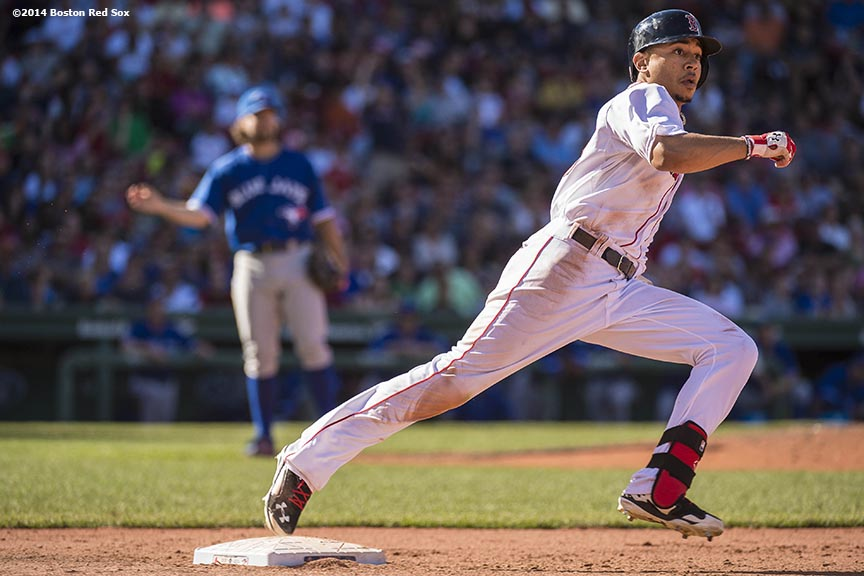 """Boston Red Sox right fielder Mookie Betts rounds first base after hitting a double during the eighth inning of a game against the Toronto Blue Jays Sunday, September 7, 2014 at Fenway Park in Boston, Massachusetts."""