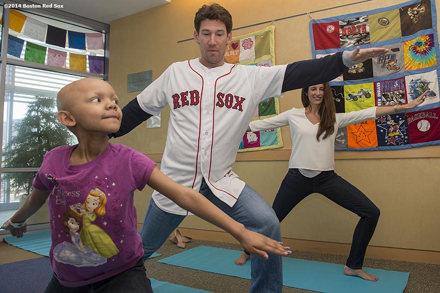 """Boston Red Sox pitcher Craig Breslow and his wife, Kelly Breslow, participate in a yoga class with a patient during a visit to Boston Children's Hospital in Boston, Massachusetts Monday, September 22, 2014."""
