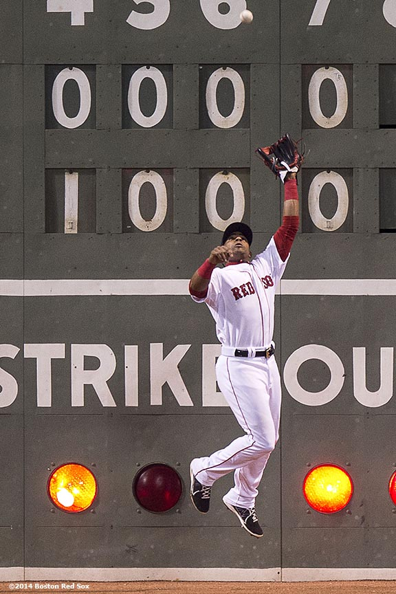 """Boston Red Sox left fielder Yoenis Cespedes misses a catch during the eighth inning of a game against the Tampa Bay Rays Tuesday, September 23, 2014 at Fenway Park in Boston, Massachusetts."""