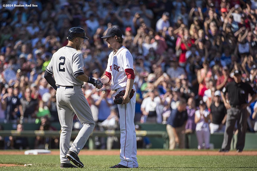 """New York Yankees shortstop Derek Jeter shakes hands with Boston Red Sox pitcher Clay Buchholz after reaching first base in his final career at bat during the third inning of a game at Fenway Park in Boston, Massachusetts Sunday, September 28, 2014. It was Jeter's last career Major League game."""
