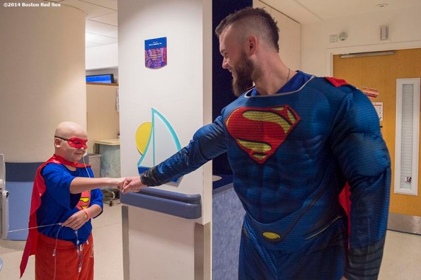 """Boston Red Sox pitcher Drake Britton wears a Superman costume for Halloween as he greets a patient at Boston Children's Hospital in Boston, Massachusetts Thursday, October 30, 2014."""