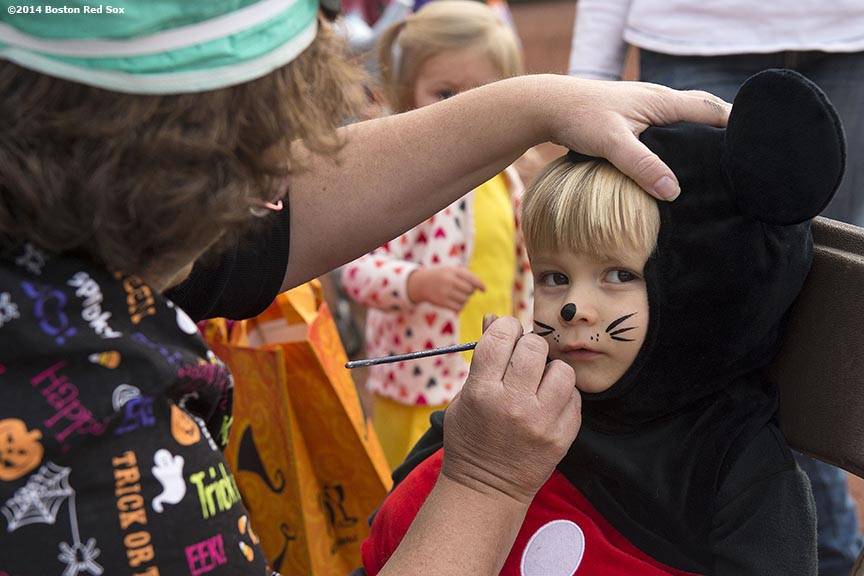 """A trick or treater gets her face painted during Halloween at Fenway at Fenway Park in Boston, Massachusetts Thursday, October 30, 2014."""