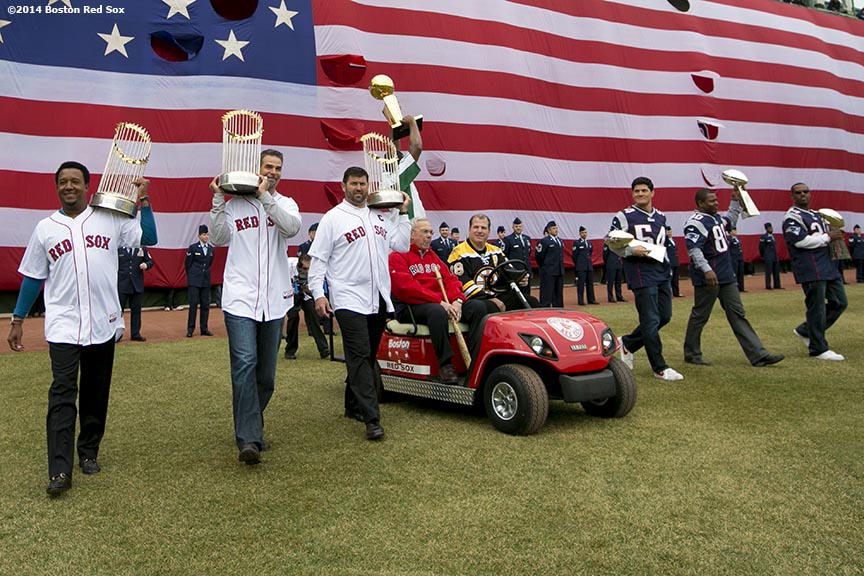 """(From left to right) Former Boston Red Sox players Pedro Martinez, Mike Lowell and Jason Varitek, former Mayor of Boston Tom Menino, former Boston Celtics player Leon Powe, former Boston Bruins player Mark Recchi, and former New England Patriots players Tedy Bruschi, Troy Brown, and Ty Law display championship trophies as they are introduced during the Boston Red Sox World Series ring ceremony at the 2014 season home opener at Fenway Park. """