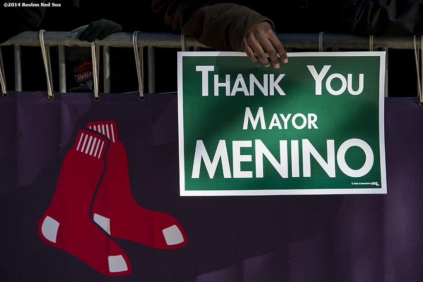 """A member of the Boston Red Sox front office holds a sign as employees line Yawkey Way to pay respects during the funeral procession for former Boston Mayor Thomas Menino at Fenway Park in Boston, Massachusetts Monday, November 3, 2014."""