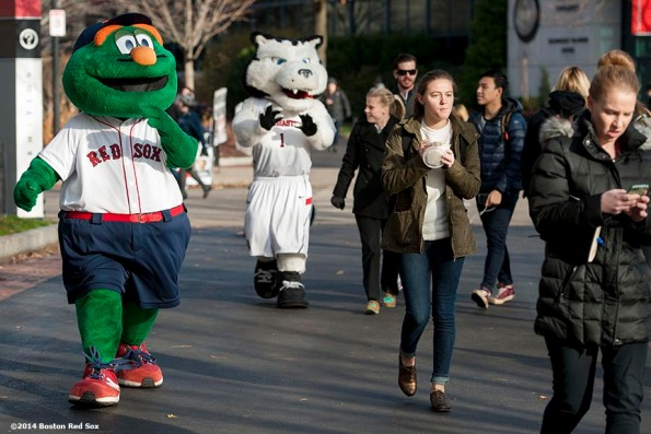 """""""Boston Red Sox mascot Wally the Green Monster and Northeastern University mascot Paws walk through campus during a Boston Red Sox Foundation fundraising event at Northeastern University in Boston, Massachusetts Thursday, December 4, 2014. """""""