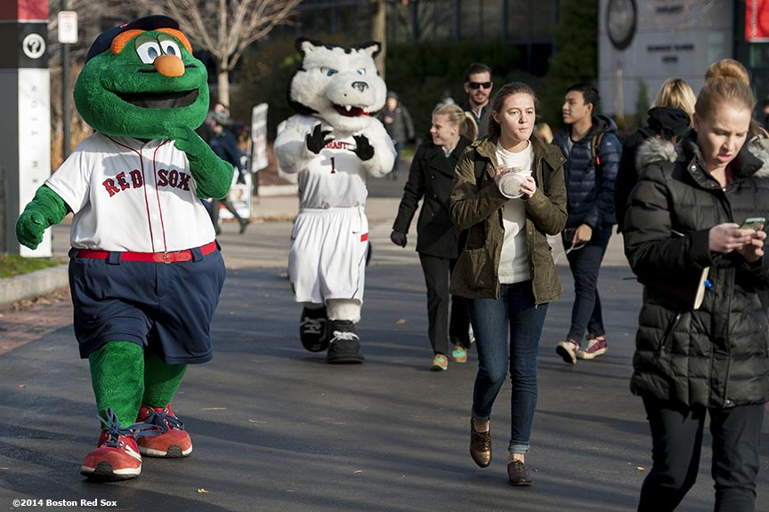 """Boston Red Sox mascot Wally the Green Monster and Northeastern University mascot Paws walk through campus during a Boston Red Sox Foundation fundraising event at Northeastern University in Boston, Massachusetts Thursday, December 4, 2014. """