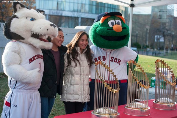"""""""Students pose with Boston Red Sox mascot Wally the Green Monster and Northeastern University with the 2004, 2007, and 2013 World Series trophies are shown during a Boston Red Sox Foundation fundraising event at Northeastern University in Boston, Massachusetts Thursday, December 4, 2014."""""""