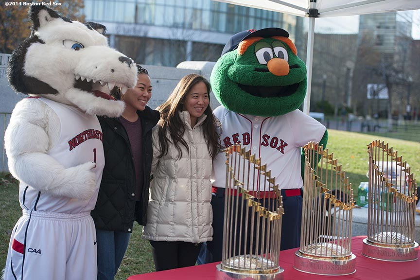 """Students pose with Boston Red Sox mascot Wally the Green Monster and Northeastern University with the 2004, 2007, and 2013 World Series trophies are shown during a Boston Red Sox Foundation fundraising event at Northeastern University in Boston, Massachusetts Thursday, December 4, 2014."""