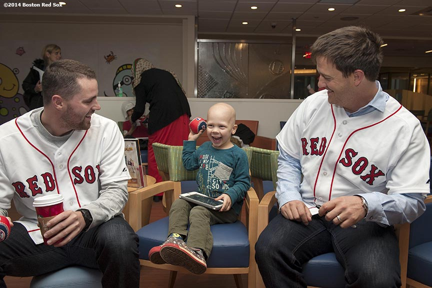 """Boston Red Sox pitchers Heath Hembree and Steven Wright visit a patient at the Jimmy Fund at Dana-Farber Cancer Institute as part of the Red Sox Holiday Caravan Thursday, December 11, 2014 in Boston, Massachusetts."""