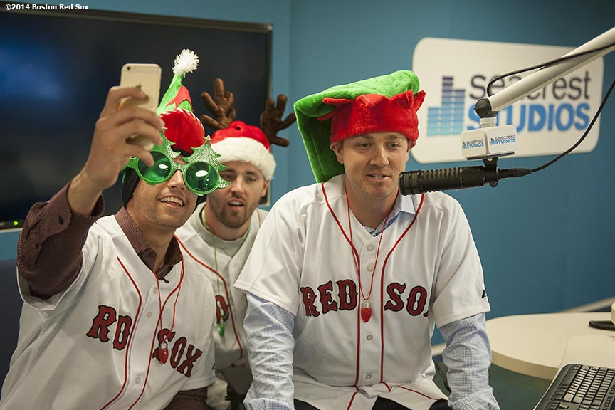 """Boston Red Sox infielder Garin Cecchini(left), and pitchers Heath Hembree (center) and Steven Wright (right) pose for a selfie photograph as they record a holiday greeting message for patients at Boston Children's Hospital as part of the Red Sox Holiday Caravan Thursday, December 11, 2014 in Boston, Massachusetts."""