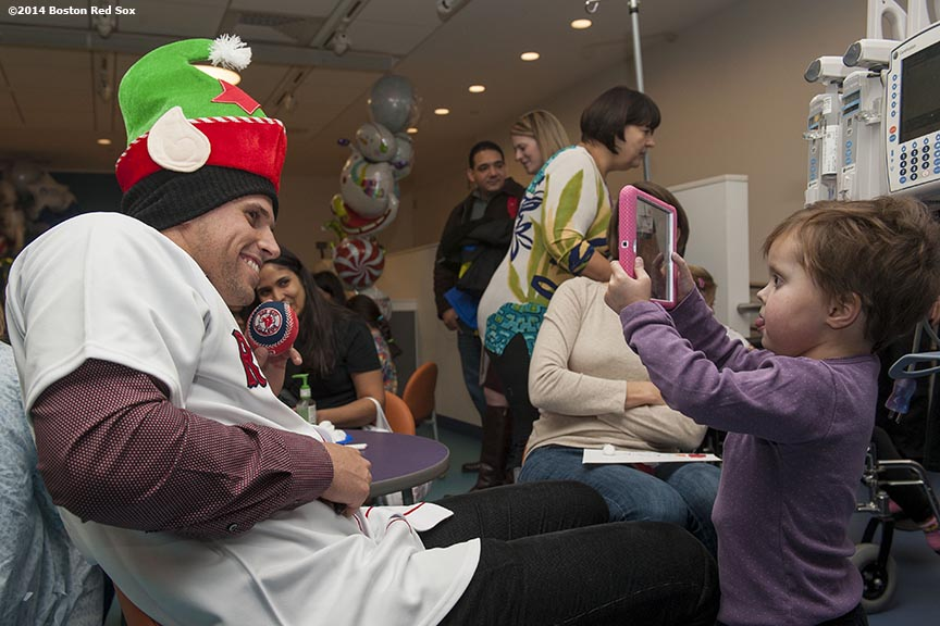"""A young patient takes a photo with an iPad of Boston Red Sox infielder Garin Cecchini during a visit to Boston Children's Hospital as part of the Red Sox Holiday Caravan Thursday, December 11, 2014 in Boston, Massachusetts."""