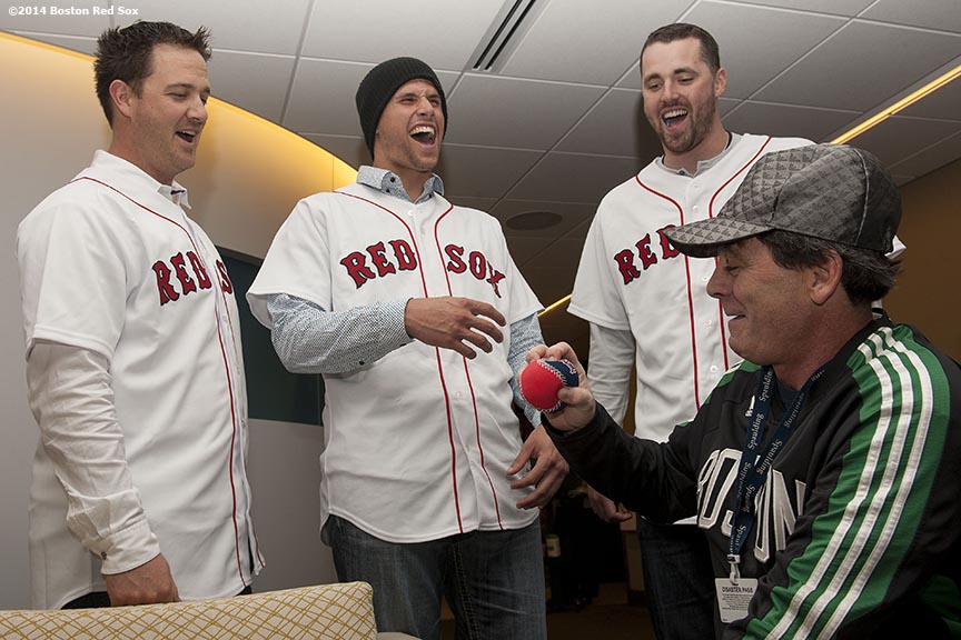 """Boston Red Sox pitcher Steven Wright (left), infielder Garin Cecchini (center), and pitcher Heath Hembree (right) laugh with a patient during a visit to Spaulding Rehabilitation Center as part of the Red Sox Holiday Caravan Friday, December 12, 2014 in Boston, Massachusetts."""