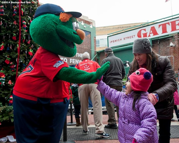 """""""A fan high fives Boston Red Sox mascot Wally the Green Monster during Christmas At Fenway Saturday, December 13, 2014 at Fenway Park in Boston, Massachusetts."""""""
