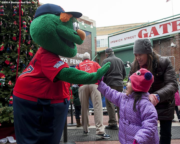 """A fan high fives Boston Red Sox mascot Wally the Green Monster during Christmas At Fenway Saturday, December 13, 2014 at Fenway Park in Boston, Massachusetts."""
