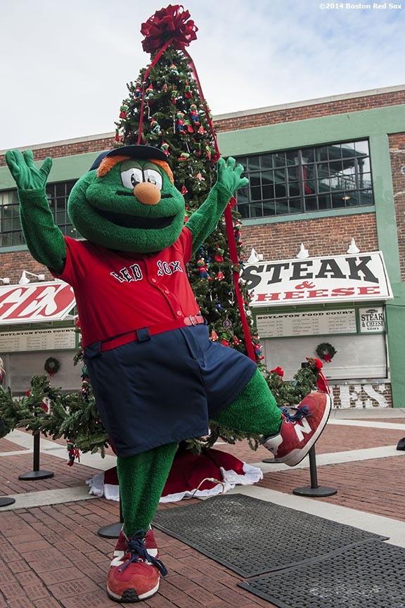 """Boston Red Sox mascot Wally the Green Monster poses for a photograph in front of a Christmas tree during Christmas At Fenway Saturday, December 13, 2014 at Fenway Park in Boston, Massachusetts."""
