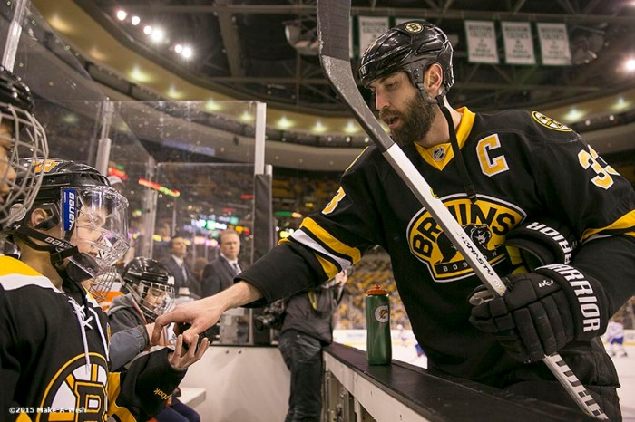 """""""Make-A-Wish recipient Jimmy Bjorkman of West Salem, Wisconsin receives a puck from Boston Bruins player Zdeno Chára as he watches warm ups from the bench before a hockey game between the Boston Bruins and the Montreal Canadiens at TD Garden in Boston, Massachusetts Sunday, February 8, 2015."""""""
