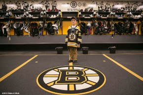 """Make-A-Wish recipient Jimmy Bjorkman of West Salem, Wisconsin poses in the Boston Bruins locker room after a hockey game between the Boston Bruins and the Montreal Canadiens at TD Garden in Boston, Massachusetts Sunday, February 8, 2015."""